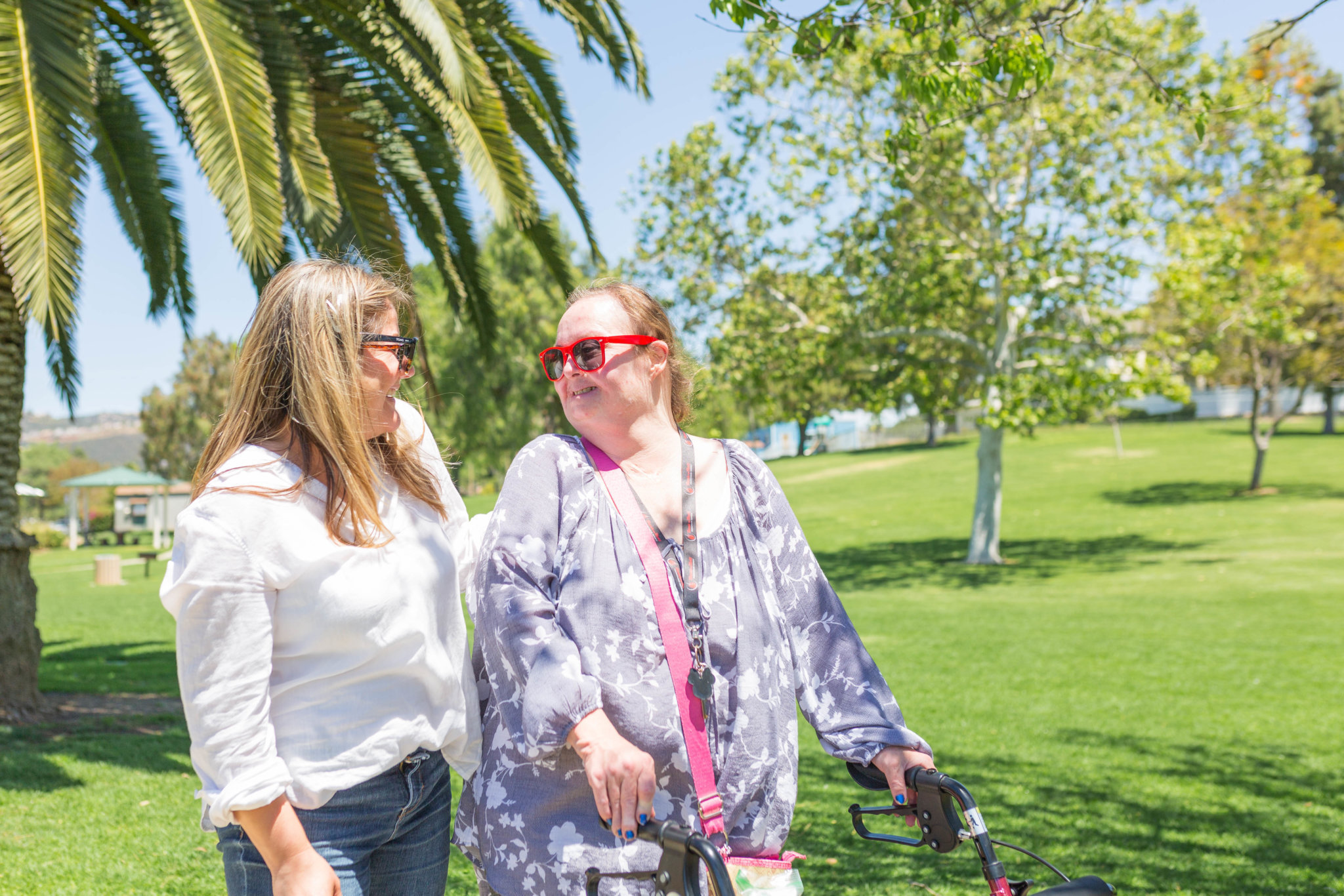 A caregiver and client walk next to each other outside in the park.