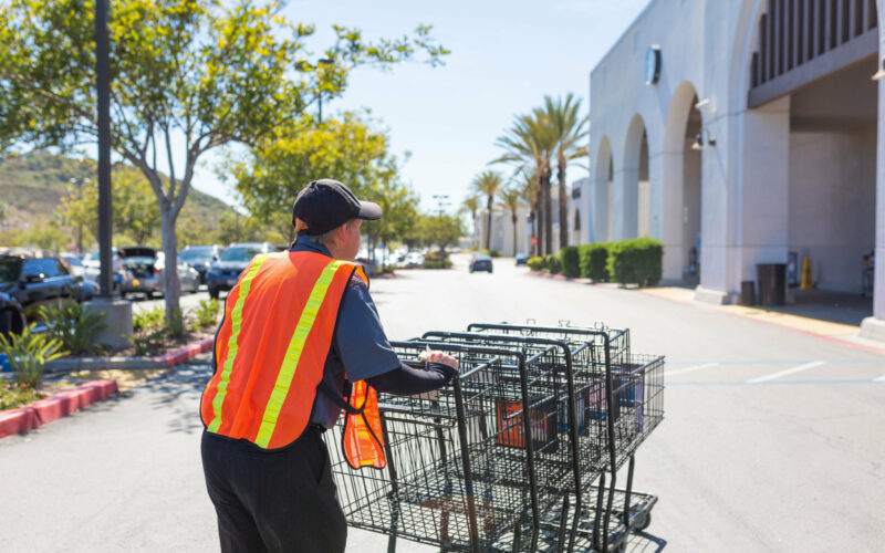 A client pushes shopping carts in a parking lot outside the grocery store.